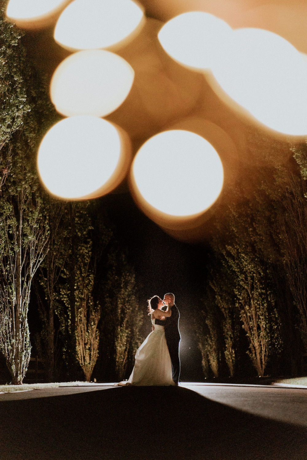 Beautiful romantic evening photograph of bride and groom holding each other about to kiss