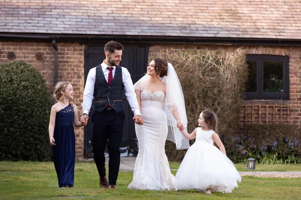 Bride and groom holding hands with flower girls