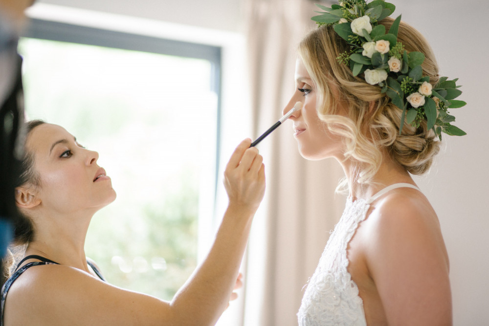 Beautiful bride having makeup finishing touches by Melissa Clare hair and makeup artist