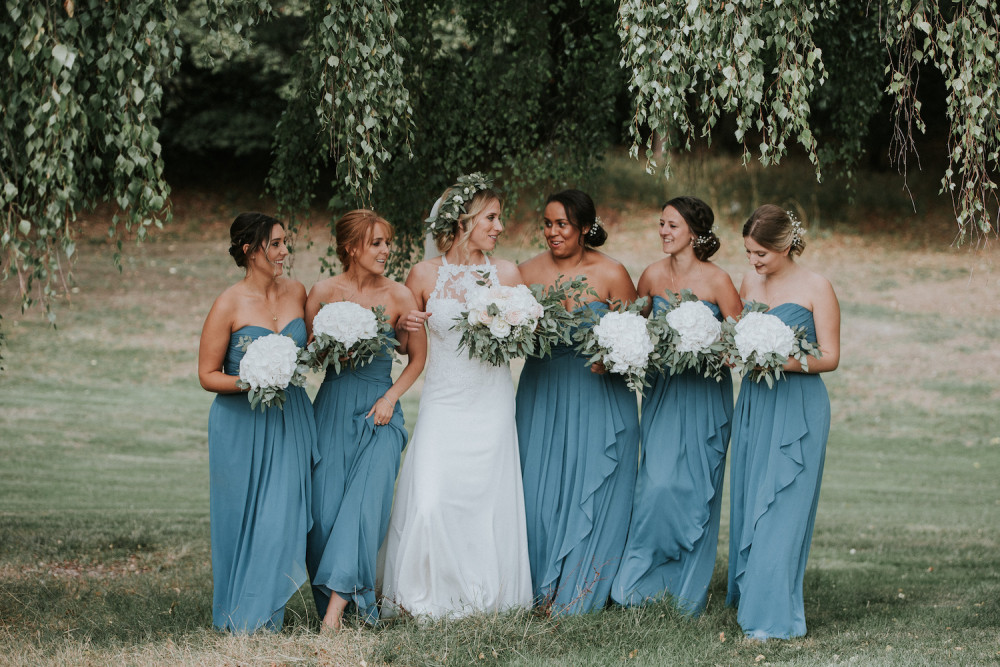 Bride and Bridesmaids holding matching flowers smiling in garden