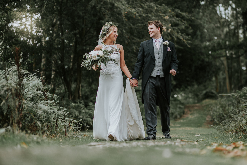 Boho bride with beautiful hair, rustic leafy flowers and happy groom holding each other smiling for their wedding day photoshoot