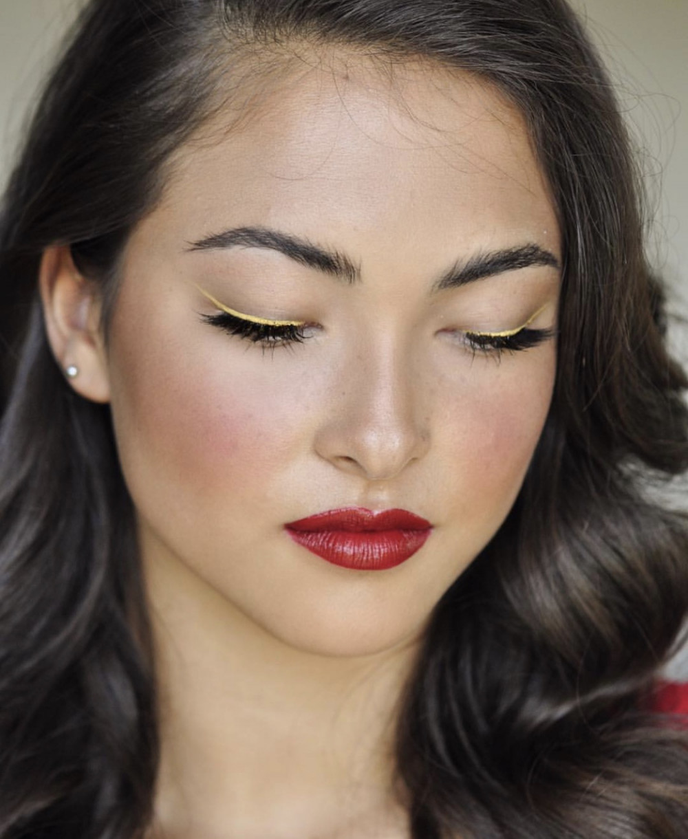 Bridal makeup look with red lips and yellow gold eyeliner on brunette model