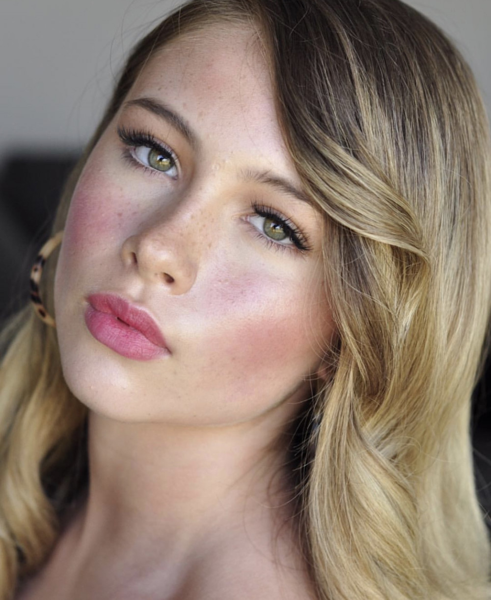 Beautiful summer bridal makeup with pink cheeks and freckles on bride with green eyes