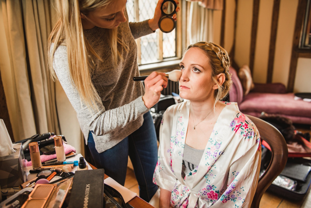 Makeup artist applying bridal makeup and bronzer to the bride on her wedding morning