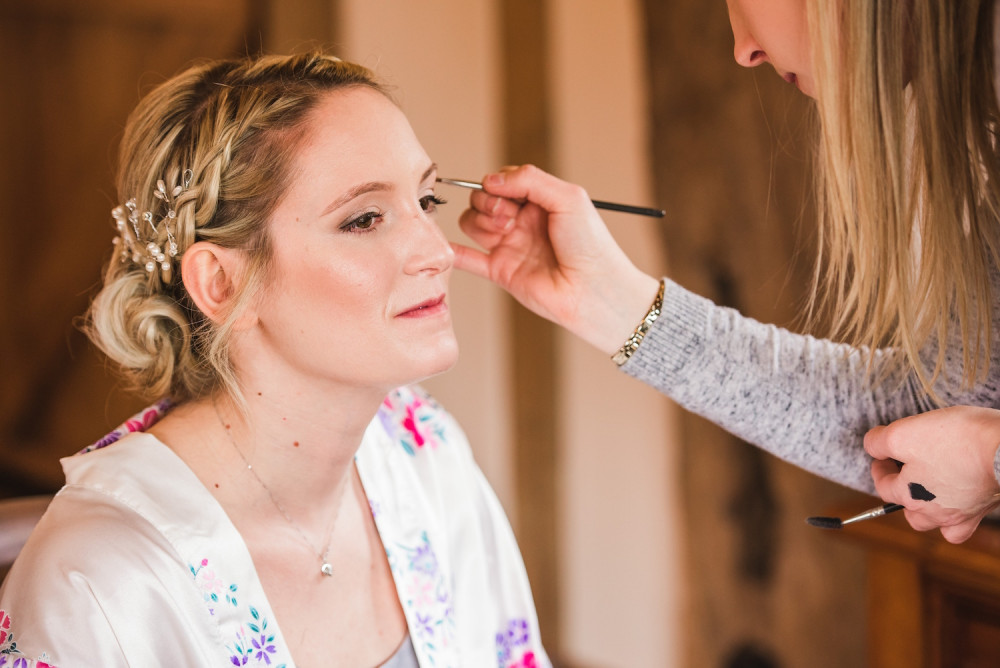 Makeup artist applying bridal makeup and eyeshadow to the bride on her wedding morning.