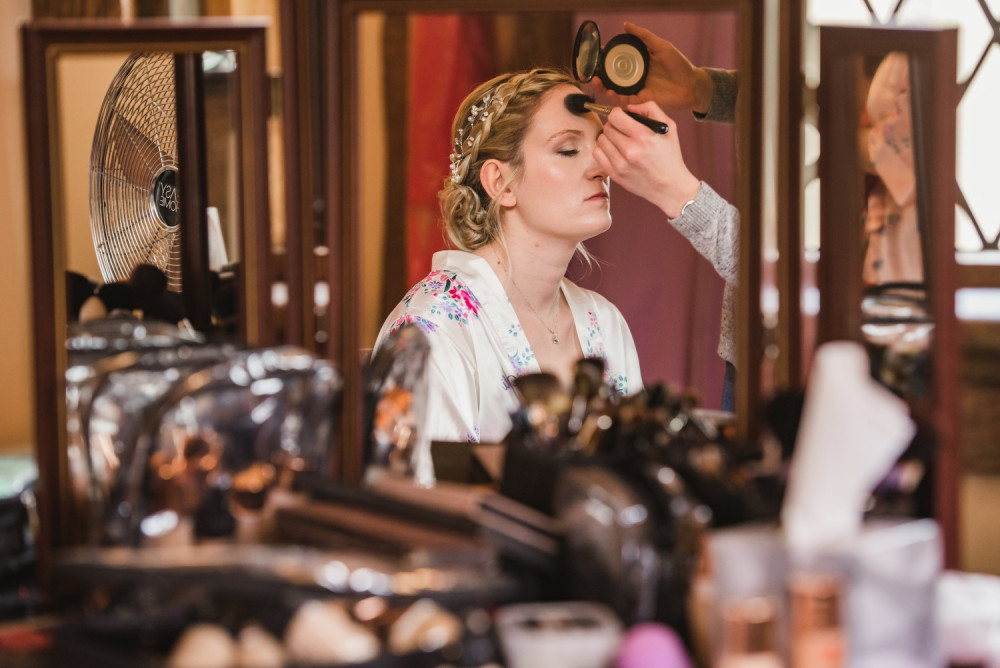 Makeup artist applying bridal makeup and powder to the bride on her wedding morning.