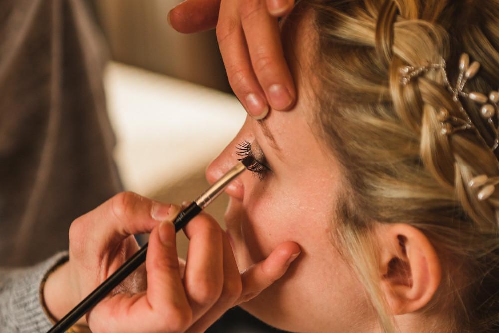 Makeup artist applying bridal makeup and eyeliner to the bride on her wedding morning
