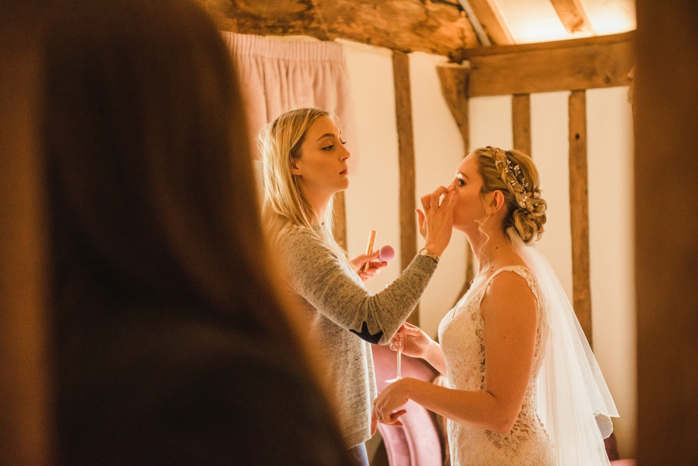 Makeup artist applying bridal makeup, blusher and final touch ups to the bride on her wedding morning