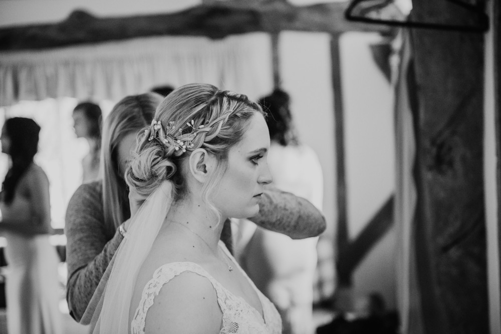 Beautiful wedding updo hairstyle with plaits and pretty silver bridal hairvine with hairstylist attaching the veil