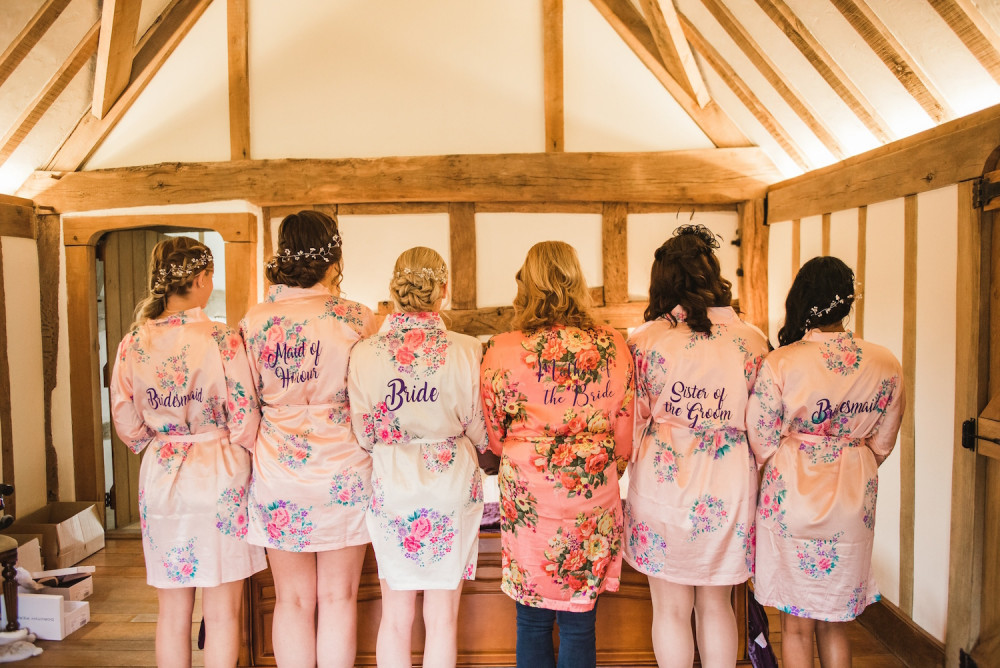Bridesmaids and the bride on her wedding morning wearing bridal dressing gowns.