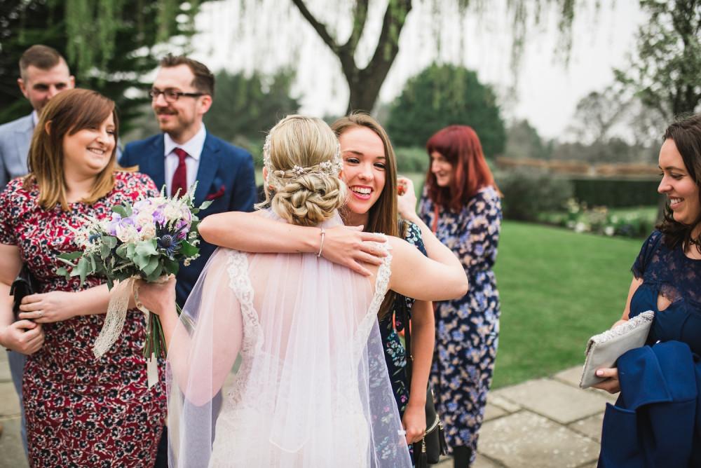 Bride wearing veil greats her wedding guests