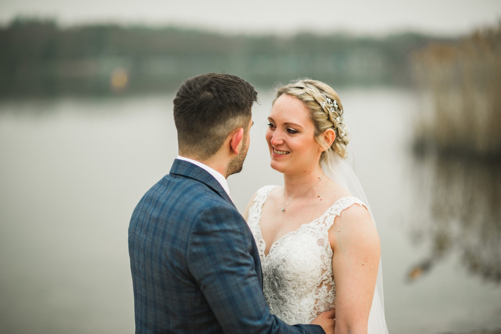 Happy Bride and Groom embrace by a lake on their wedding day