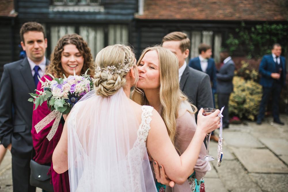 Bride wearing veil greets her wedding guests
