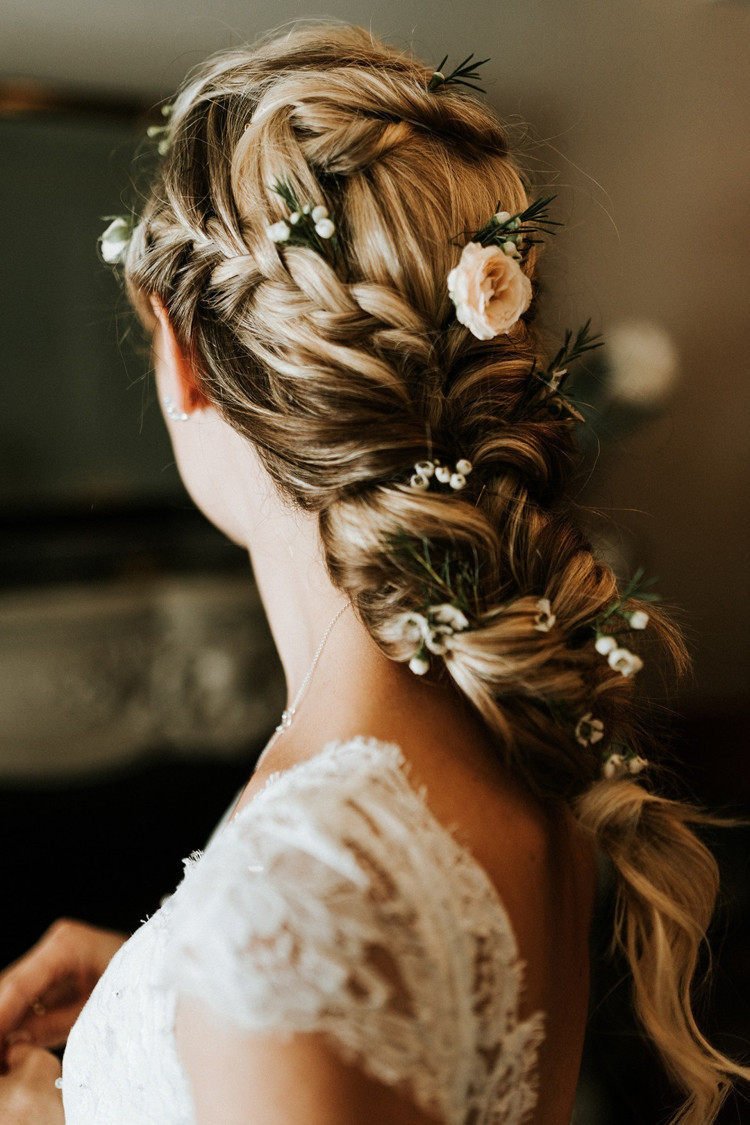 Beautiful bridal hairstyle with loose tousled plait worn with fresh roses