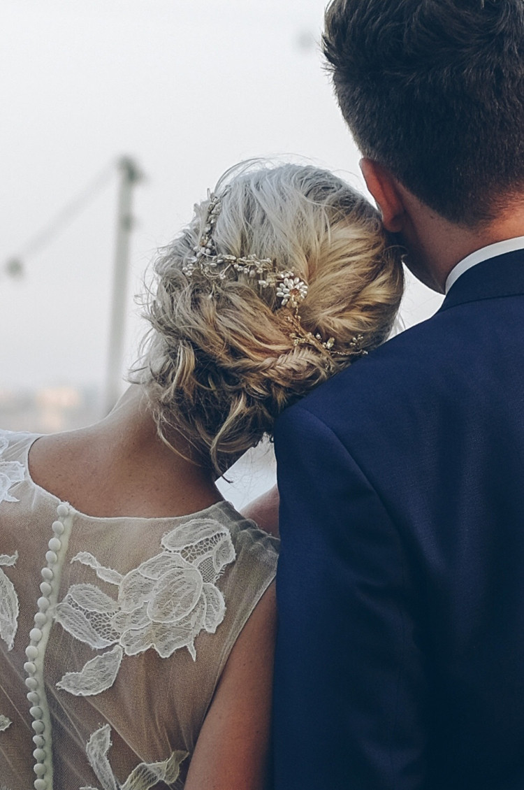 Blonde bride with hair up and pretty hair vine embracing groom