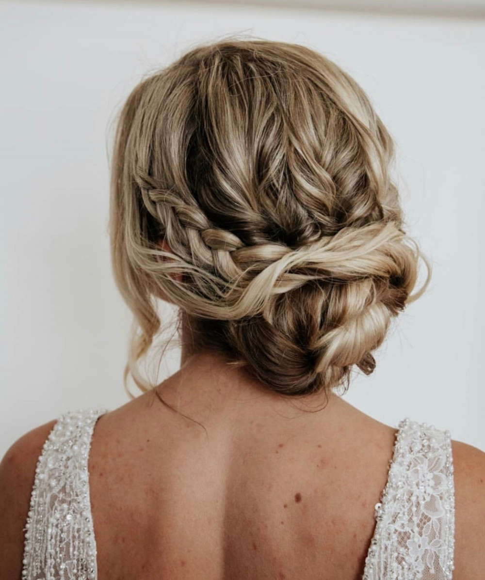 Tousled bun with texture and plaits on blonde bride with highlights