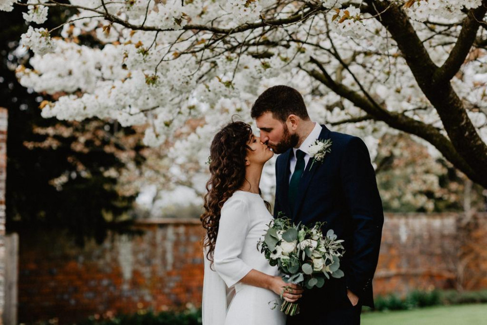 Bride and groom kissing in spring garden with cherry blossom trees
