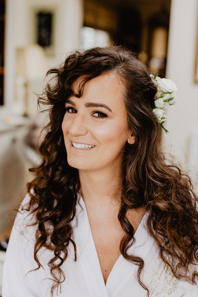 Brunette curly haired bride with white roses in hair and beautiful makeup