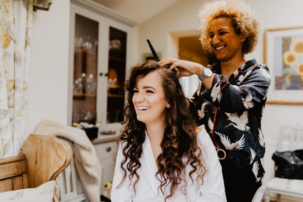Happy bride laughing whilst having hair styled by hair stylist on her wedding day