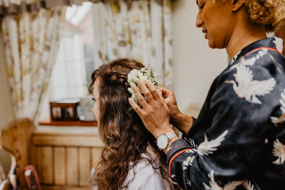 Bride having hair styled with white roses by wedding hair stylist