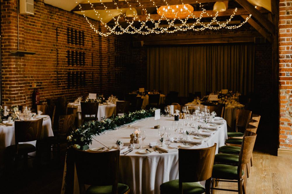 Wedding breakfast room with fairylights and green foliage