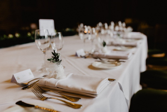 Wedding breakfast table with wine glasses and foliage