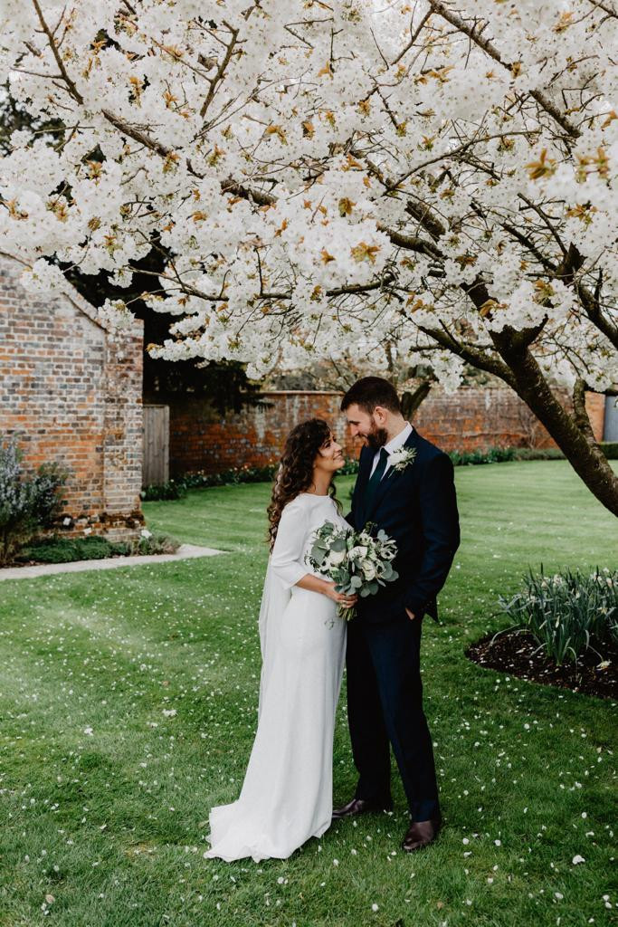 Bride and groom embrace under a cherry blossom tree