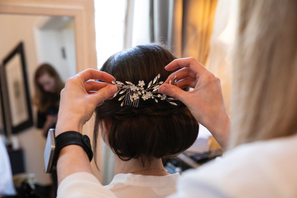 A shot of me putting the final finishing touches to Megan's hair which lasted all day, all night and all the next day - Make Me Bridal Artist: Hair Design by Lisa. Photography by: Lorna Newman. #classic #vintage #hairvine #weddingmorning #gettingready #meatwork #bridalhair #prep #chignon #elegant #lowupdo #hairup