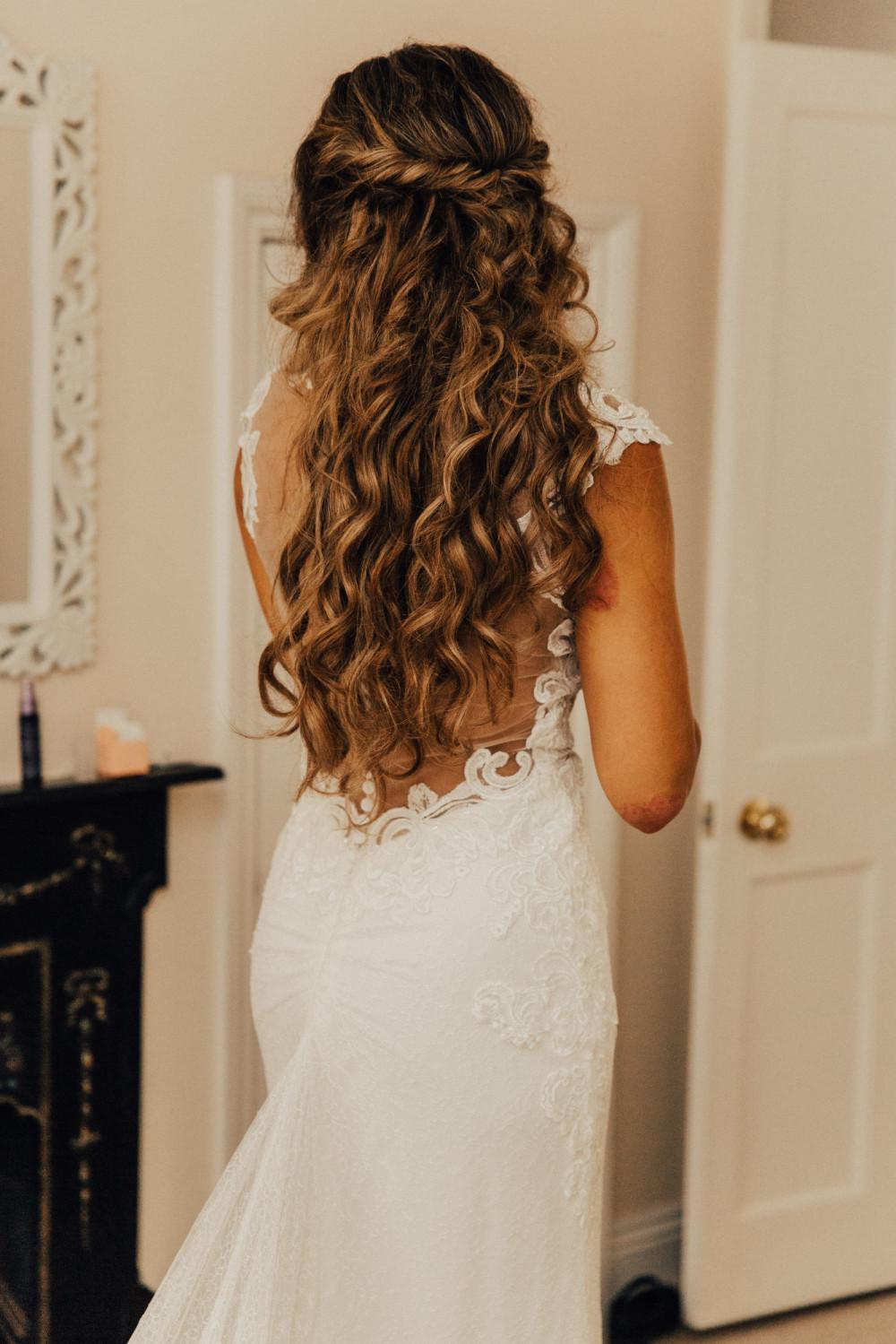 A beautiful shot of Freya in her dress showing her amazing bohemian waves. - Make Me Bridal Artist: Hair Design by Lisa. Photography by: The Wild Bride. #bohemian #boho #halfuphair #curls #weddingmorning #gettingready #bridalhair #rustic #brunette #tousled #weddinghair #bridalhairstylist #wavyhair