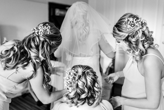 The bridesmaids all coming together to help the bride perfect her bridal look! The wedding morning is always a time when everybody pulls together. And I loved creating these beautiful shining curls for this bridal party. - Make Me Bridal Artist: Bridal Hair in Hampshire. Photography by: Lloyd Richard Photography. #glamorous #curls #gettingready #bridalhair #blonde