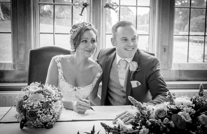 The bride and groom signing the register. - Make Me Bridal Artist: Bridal Hair in Hampshire. Photography by: Kevin Drake Photography. #weddingmorning #bridalmakeup #bridalhair