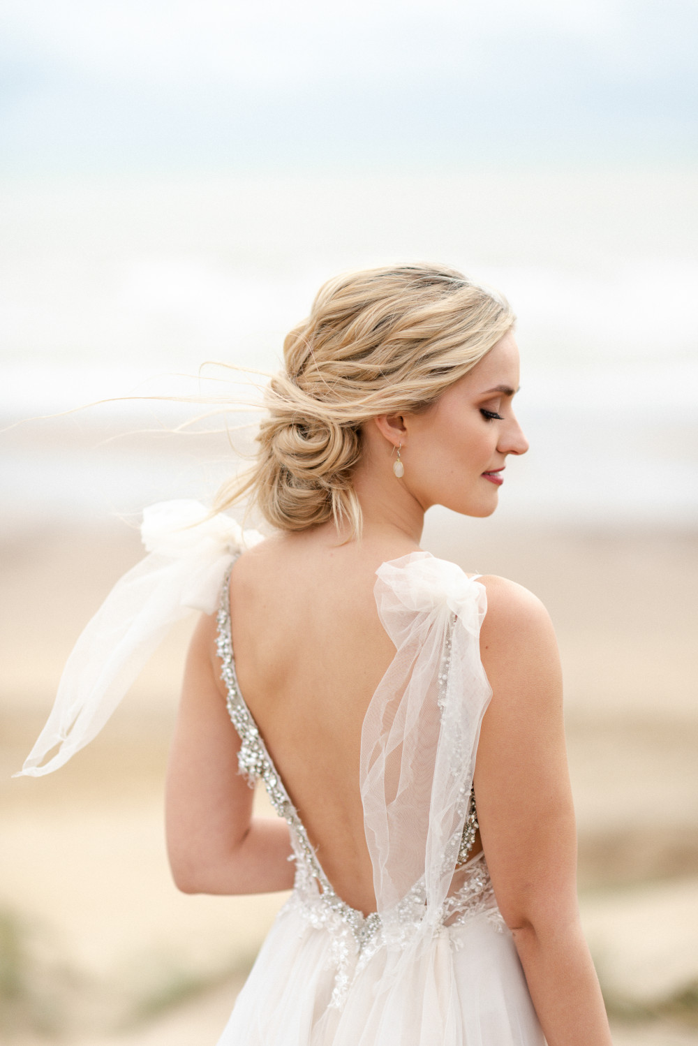 Super textured chignon with striking makeup for this beach themed photoshoot. - Make Me Bridal Artist: Laura Anne Hair & Makeup Designer. Photography by: Eva Tarnok. #beachwaves #modernbride #texturedupdo #beachwedding