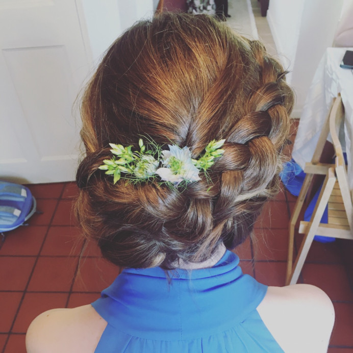 A lovely low bun to the side with a braid going into it - Make Me Bridal Artist: Wild Rose Hair . #boho #lowupdo #relaxedupdo #hairup #braid #messybun #bridesmaidhair
