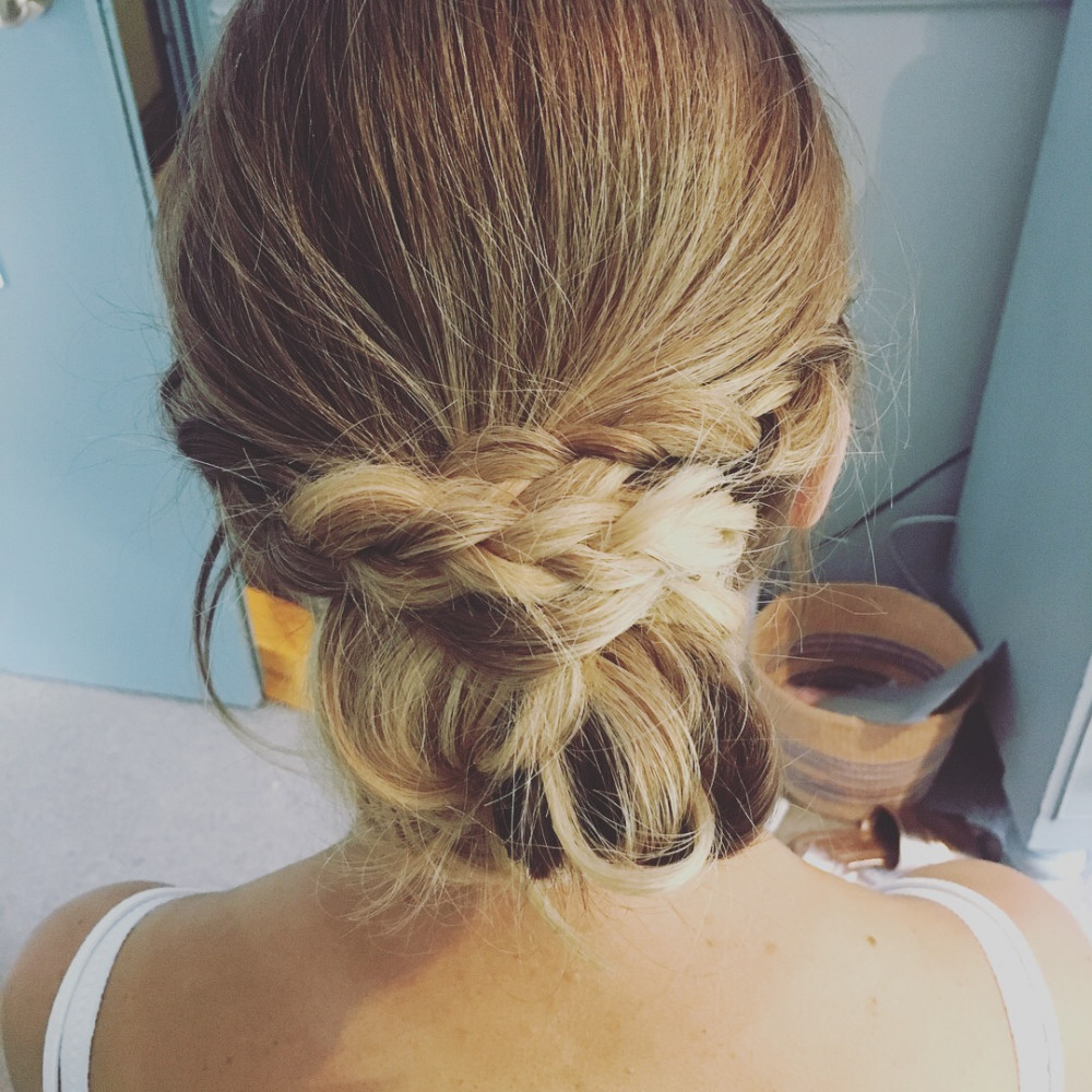 A low messy bun with braid going into it - Make Me Bridal Artist: Wild Rose Hair . #lowupdo #braid #messybun #braidedupdo #bun