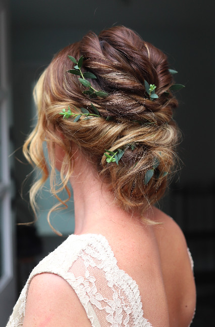 A messy bun decorated with foliage - Make Me Bridal Artist: Katy Djokic - Wedding Hair & Makeup. #bohemian #updo #rustic #messybun #bohohair