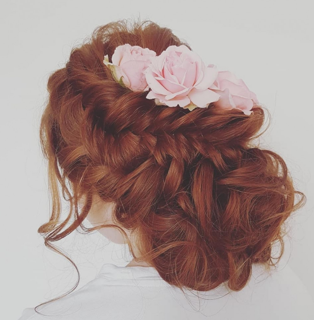 Beautiful big hair. Loosely pinned curls. Chunky fish plait to give detail. Real roses to finish this style off. - Make Me Bridal Artist: Hair Creations North West. #curls #roses #flowersinherhair #hairup #lowbun #weddinghair #fishtailbraid #bridalhair #bighair #glambride #volume #mobilehairstylist #rosesinhair