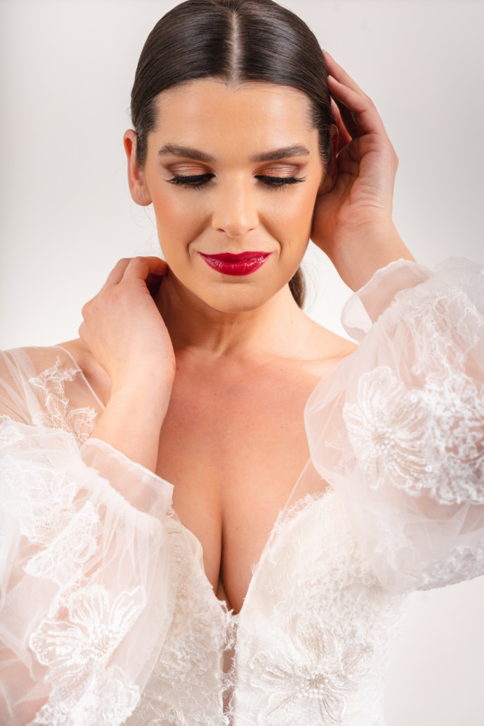 Make a statement with a stunning red lip against flawless skin - Make Me Bridal Artist: In the Bridal Chair. Photography by: Timothy James. #bridalmakeup #bridalhair #weddinghairandmakeup #redlip #glamourous #flawlessmakeup #dewyskin #glambride #beautifulbridalmakeup #glowingskin #softmakeup