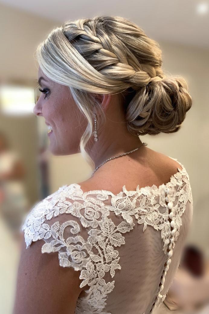 Bridal hair, a low bun with plait. - Make Me Bridal Artist: Hair That Turns Heads. Photography by: Hair That Turns Heads. #classic #glamorous #weddingmorning #gettingready #bridalhair #blonde #braid #plaits #lowbun #plaitupdo #twistedupdo #romantichair #surreywedding #surreybridalhair