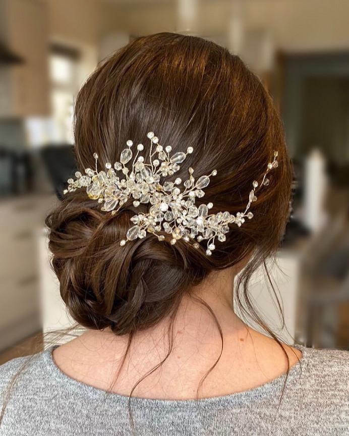 Bridal hair trial. Textured low bun updo, Boho style with hair accessory. - Make Me Bridal Artist: Nipona Khan Professional Hair & Makeup Artist. #classic #glamorous #bridalhair #elegant #romantichairup #bohobride #bridalhairup #hairaccessories #brunettebride #lowbun #twistedbun #bridalbun #brunettehair #lowupdo