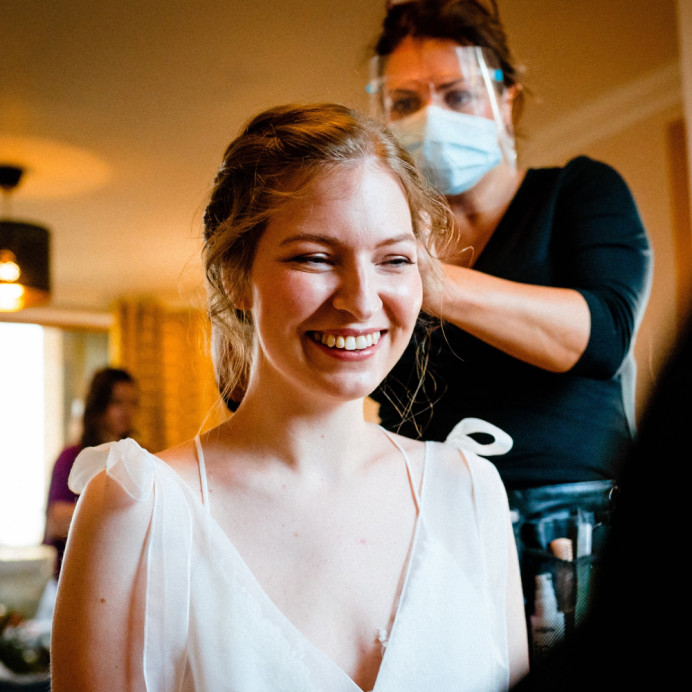 Getting ready on the wedding morning.  Following hygiene guidelines, wearing mask and visor - Make Me Bridal Artist: Amanda Roberts Hair & Makeup. Photography by: Paul Rogers. #naturalmakeup #weddingmorning #gettingready #updo #weddinghairandmakeup #weddingmakeup #happybride #healthyglow