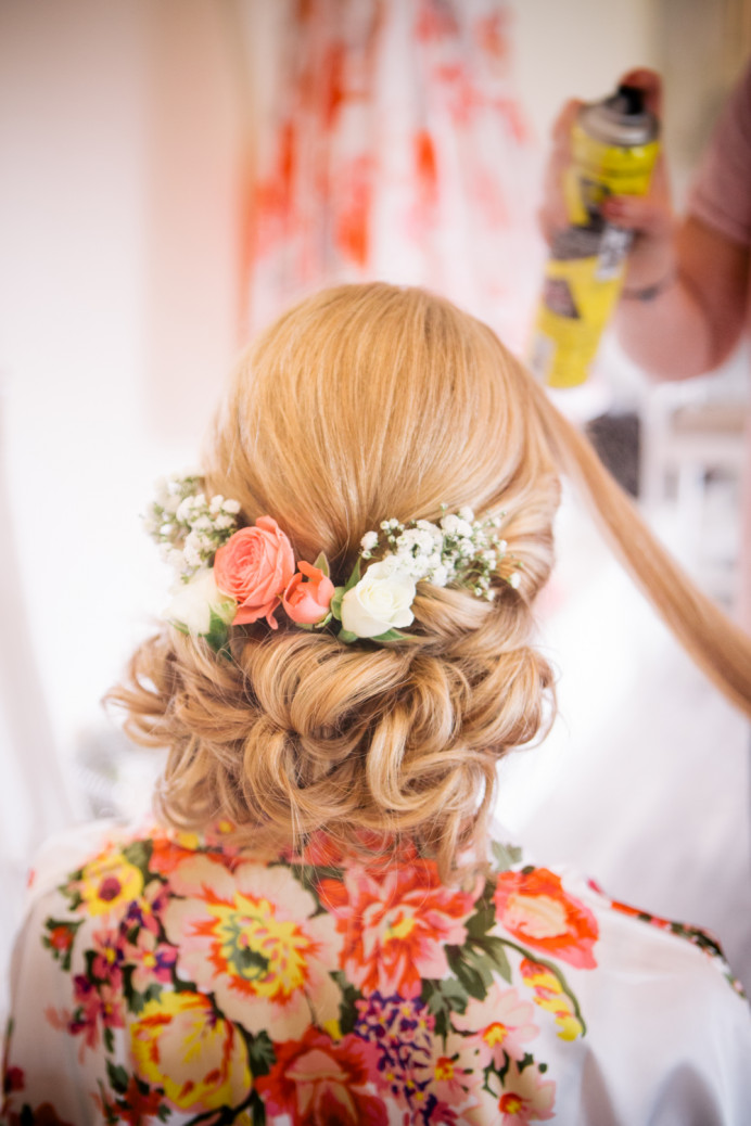 Low curled updo, decorated with flowers - Make Me Bridal Artist: Story Hair and Makeup. Photography by: Katie Hamilton. #vintage #boho #curls #weddingmorning #bridalhair #flowersinherhair #lowupdo